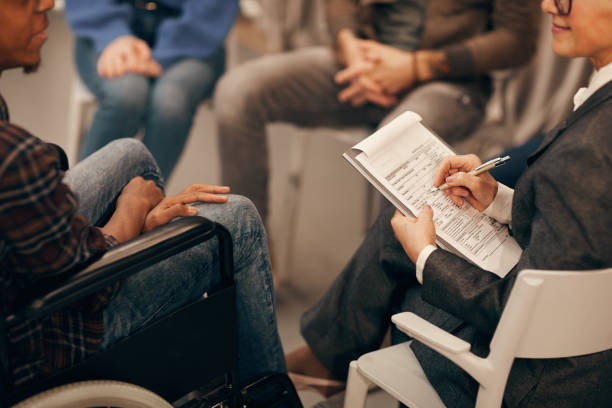Close-up of mature woman sitting on chair and filling some form while young man in wheelchair telling her about his problems